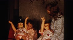 1961: two girls in robes wrestle with life-size dolls to make them sit or stand Stock Footage