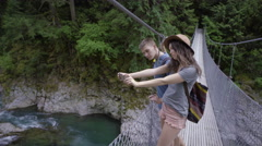 Hikers Stop On Suspension Bridge To Take Photos With A Smart Phone Stock Footage