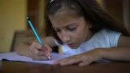 Closeup of pretty, long-haired young girl doing homework writing. Stock Footage