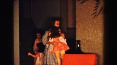 1961: two girls wearing pajamas and robes with life-size dolls  Stock Footage