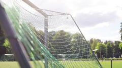 Ball flying into football goal net on field Stock Footage