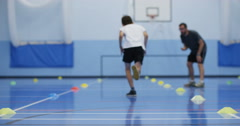 4K Sports teacher coaching young boy, running laps & working hard in school gym Stock Footage