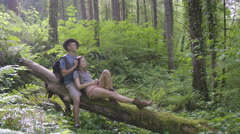 Romantic Couple Sit On A Fallen Tree In Forest, Man Strokes His Girlfriends Hair Stock Footage