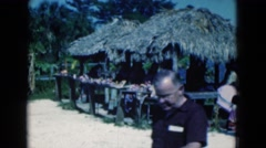 1950: man walking in front of tropical huts with a woman and child FLORIDA Stock Footage