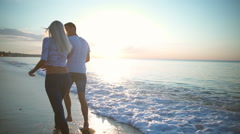 Attractive blonde girl and her boyfriend fleeing by sea at sunrise. Slow motion. Stock Footage