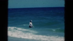 1950: an older man in a swimsuit wades in the ocean braving very tall waves Stock Footage