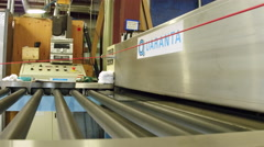 Tracking shot of glass coming out of machine in factory Stock Footage