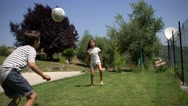 Young boy and girl playing soccer in the backyard on the lawn, barefoot. Stock Footage