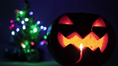 Closeup of scary holiday halloween carved glowing pumpkins. and Christmas tree Stock Footage