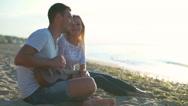 Beautiful couple smiling sitting at beach. Man playing ukulele. Slow motion. Stock Footage