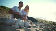 Couple smiling sitting with dog near sea. Man playing ukulele. Slow motion. Stock Footage