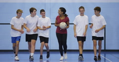 4K Female sports teacher coaching young male team on indoor soccer pitch Stock Footage