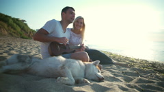 Couple smiling sitting with dog near sea. Man playing ukulele. Slow motion. Stock Footage