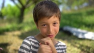 Angry young boy joking and fists in the park looking at camera. Stock Footage