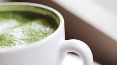 Teaspoon stirring matcha green tea latte in cup Stock Footage