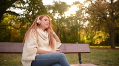 Beautiful woman listening to music on headphones Stock Footage