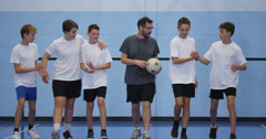 4K Sports teacher coaching young male team on indoor soccer pitch Stock Footage