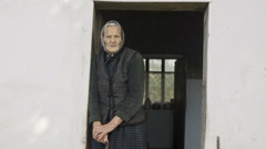 Old grandmother on a background of an old house Stock Footage