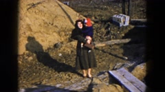 1954: a woman outdoor in a coat holding a small toddler in her arms HICKSVILLE Stock Footage