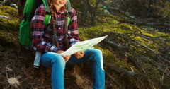 Young hiker girl using her map and sitting in the forest. Panning Stock Footage
