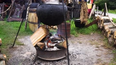 Cooking In a camp In The Cauldron Over fire Stock Footage