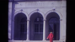 1972: a woman in a long red jacket walking into a primate's building WISCONSIN Stock Footage