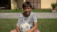 Young boy holding a soccer ball in the backyard and smiling. Stock Footage