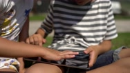 Closeup of little boy and girl's using digital tablet in the backyard. Stock Footage
