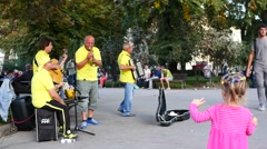 Little child kid girl throw money to street music band buskers in Sofia Bulgaria Stock Footage