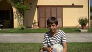 Young boy playing with a soccer ball in the backyard and smiling. Stock Footage