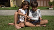 Little boy and girl using digital tablet on the lawn, in the backyard. Stock Footage