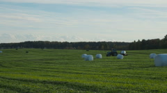 Tractor wrapping a bale of hay after collecting the dried hay on a field Stock Footage