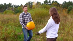 Man bring big pumpkin and give wife, woman take large squash with difficulty Stock Footage