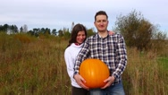 Adorable young family stay in field with big harvested pumpkin, thumbs up Stock Footage