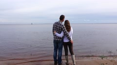 Romantic pair stand on lake coast, kiss and hug, look at distance Stock Footage