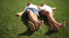 Closeup, barefoot little boy and girl lying on the lawn and moving feet. Stock Footage