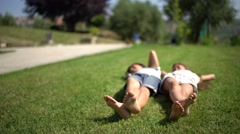 Barefoot little boy and girl lying on the lawn and moving feet. Stock Footage