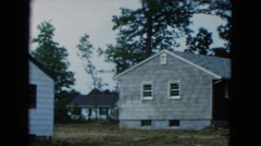 1954: mid-19th century group of homes in a forest with a classic automobile Stock Footage