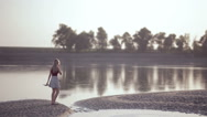 Young beautiful blonde walks by the river Stock Footage