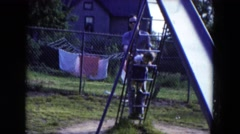1954: father plays with daughter in the backyard on a slide HICKSVILLE, NEW YORK Stock Footage
