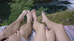 Closeup Of Adventurous Couples' Legs On Cliffside, Play Footsie, Hold Hands Stock Footage