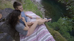 Couple Rest On A Picnic Blanket Above River, Man Brushes Back Girlfriend's Hair Stock Footage