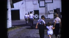 1954: various people walking towards an old tin barn or warehouse HICKSVILLE Stock Footage