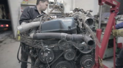 Experienced workers move the car engine Stock Footage