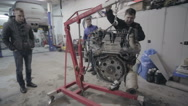 Group workers move the car engine Stock Footage