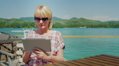 Young woman with the tablet. Sitting in a cafe on the terrace on the background Stock Footage