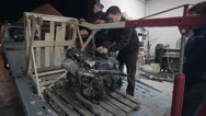 Workers group put the car engine on the truck Stock Footage