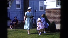 1955: a mother and her two young daughters are dressed to visit neighbor  Stock Footage