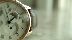 Close up of a half faced golden Wrist Watch against golden background Stock Footage