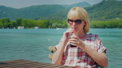 Young tourist woman relaxing in a beautiful location by the lake and mountains Stock Footage